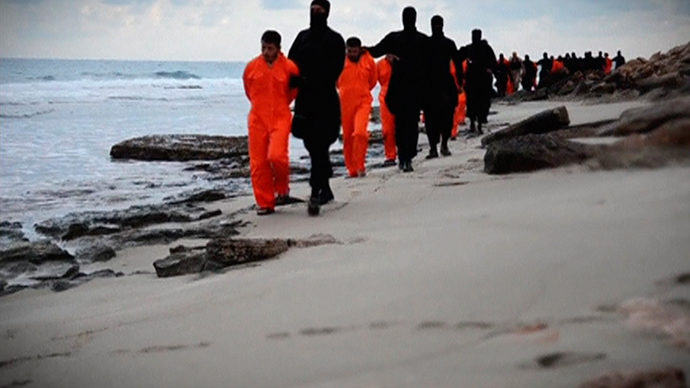Men in orange jumpsuits purported to be Egyptian Christians held captive by the Islamic State (IS) are marched by armed men along a beach said to be near Tripoli, in this still image from an undated video made available on social media (Reuters / Social media via Reuters TV)