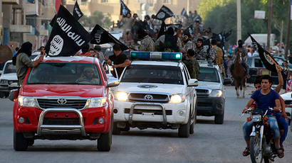 Militant Islamist fighters waving flags, travel in vehicles as they take part in a military parade along the streets of Syria's northern Raqqa province June 30, 2014 (Reuters)