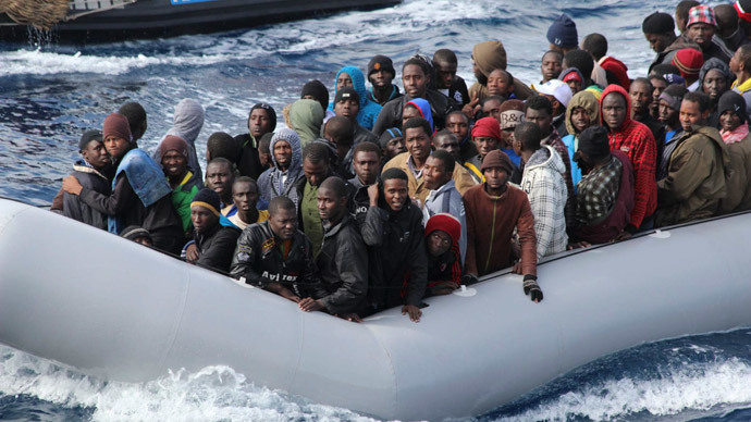 Migrants sit in a boat during a rescue operation by Italian navy off the coast of the south of the Italian island of Sicily.(Reuters / Marina Militare)