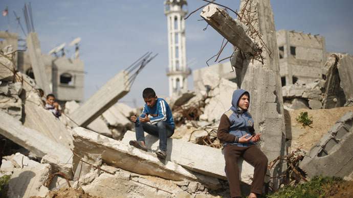 Palestinian boys attend Friday prayers as they sit at the remains of a house that witnesses said was destroyed by Israeli shelling during a 50-day war last summer, in the Shejaia neighbourhood east of Gaza City January 23, 2015. (Reuters/Suhaib Salem)