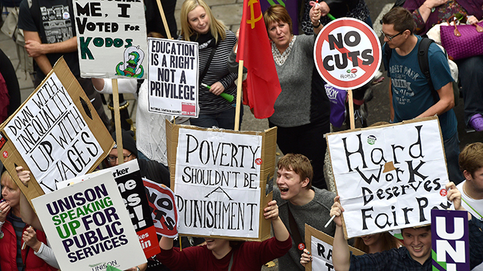 Protestors hold placards as they march through central London, October 18, 2014 (Reuters / Toby Melville)