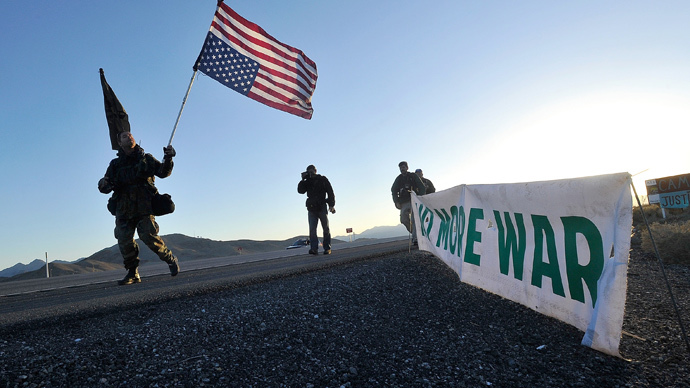 Protestor carries an American Flag upside down as members and supporters of the activist group Code Pink stage a peace march and civil resistance outside Creech Air Force Base in Clark County, Nevada March 6, 2015. (Reuters / David Becker)
