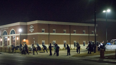 Police stand guard moments after gun shots were fired outside the City of Ferguson Police Department and Municipal Court in Ferguson, Missouri, early March 12, 2015 (Reuters / Kate Munsch)