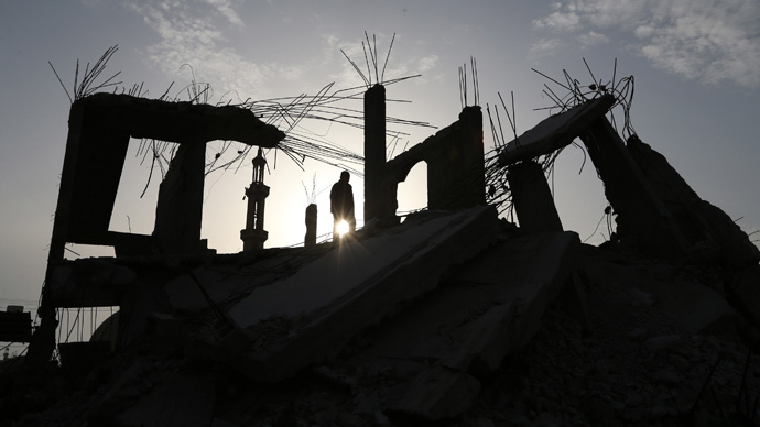 A Palestinian man walks atop the remains of a house, that witnesses said was destroyed by Israeli shelling during a 50-day war last summer, in Khan Younis in the southern Gaza Strip, March 10, 2015. (Reuters / Ibraheem Abu Mustafa)