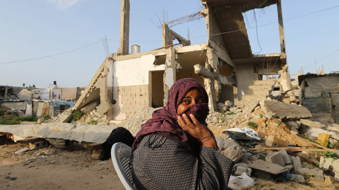 A Palestinian woman sits near her house, that witnesses said was destroyed by Israeli shelling during a 50-day war last summer, in Khan Younis in the southern Gaza Strip, March 10, 2015. (Reuters / Ibraheem Abu Mustafa)