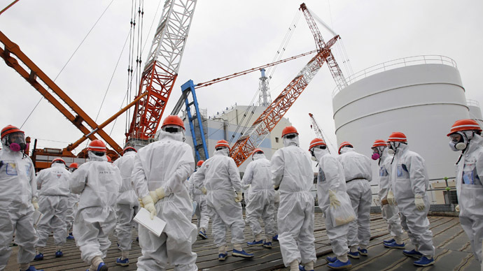 Members of the media and Tokyo Electric Power Co. (TEPCO) employees wearing protective suits and masks walk toward the No. 1 reactor building.(Reuters / Toru Hanai)