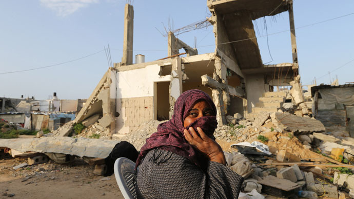 A Palestinian woman sits near her house, that witnesses said was destroyed by Israeli shelling during a 50-day war last summer, in Khan Younis in the southern Gaza Strip (Reuters/Ibraheem Abu Mustafa)