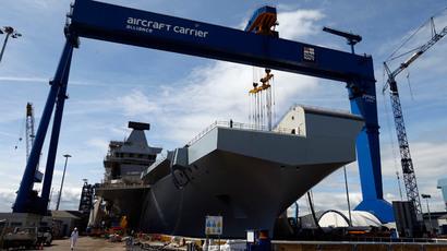 Workers walk in front of HMS Queen Elizabeth.(Reuters / Russell Cheyne)
