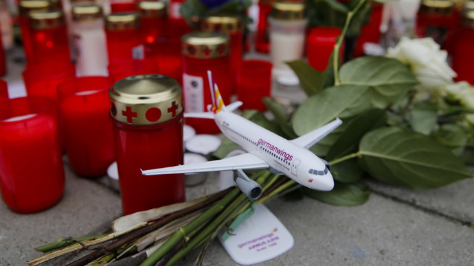 Flowers and lit candles are placed on the ground in Cologne Bonn airport, March 26, 2015. (Reuters / Wolfgang Rattay)