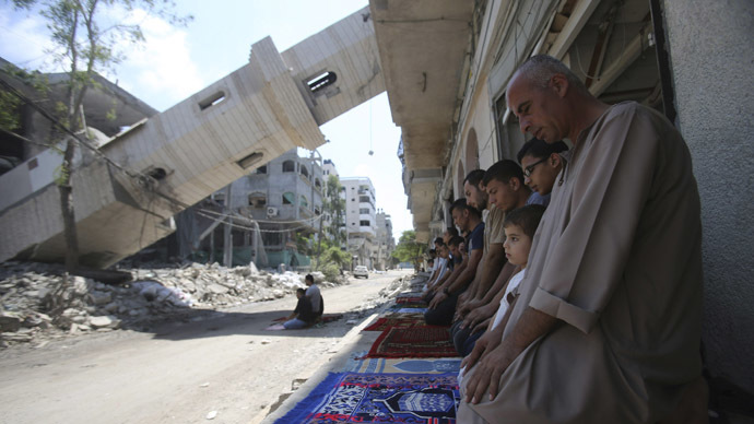 A collapsed minaret is seen as Palestinians perform Friday prayers outside the remains of a mosque, which witnesses said was hit by an Israeli air strike during a seven-week Israeli offensive in Gaza City August 29, 2014. (Reuters / Ibraheem Abu Mustafa)