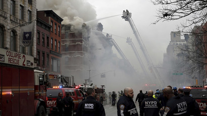 New York City Fire Department firefighters and police stand by as firefighters fight a fire at a residential apartment building in New York City March 26, 2015.(Reuters / Mike Segar)