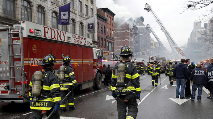 New York City Fire Department firefighters walk on 2nd Avenue towards the site of where a residential apartment was engulfed in flames in New York City March 26, 2015. (Reuters / Mike Segar)