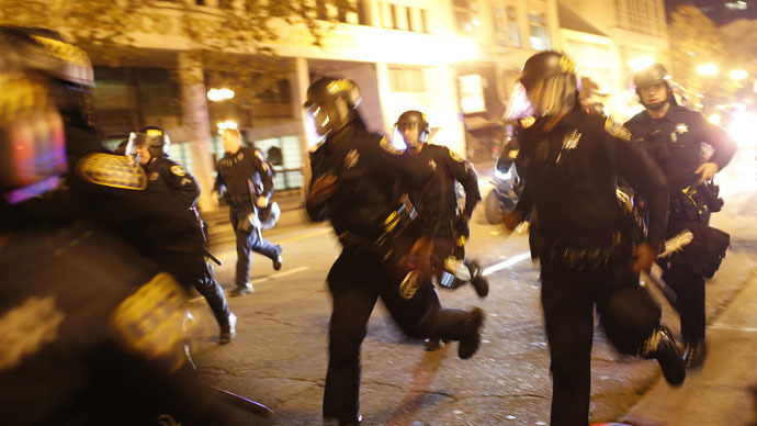 Police officers run towards protesters after a demonstration turned violent, following the grand jury decision in the Ferguson, Missouri, shooting of Michael Brown, in Oakland, California, November 26, 2014. (Reuters/Stephen Lam)