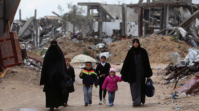 Palestinians walk near the ruins of houses in Gaza City (Reuters / Ibraheem Abu Mustafa)