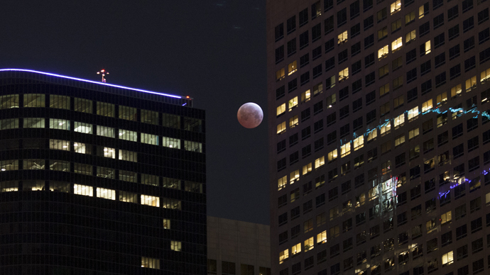 The moon is seen behind downtown high-rise buildings during the shortest total lunar eclipse of the century before dawn on April 4, 2014 in Los Angeles, California. (David McNew / Getty Images / AFP)