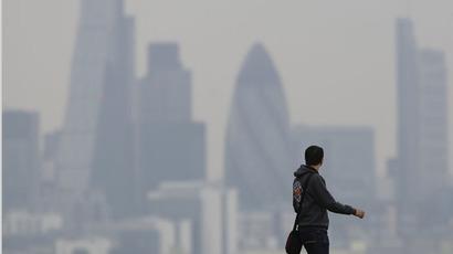 A man walks through Greenwich Park as a haze of pollution sits over the London skyline April 3, 2014. (Reuters/Luke MacGregor)
