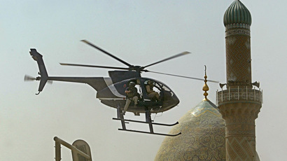 A helicopter of Blackwater security firm flies low above the scene where a roadside bomb exploded near the Iranian embassy in central Baghdad, 05 July 2005. (AFP Photo/Yuri Cortez)