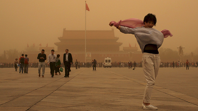 A tourist gestures as she poses for a photograph at Tiananmen Square during a sandstorm in Beijing, April 15, 2015 (Reuters / China Daily)