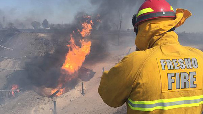 A firefighter watches the blaze after a gas line exploded near Fresno, California April 17, 2015. (Reuters/Fresno Fire Department)