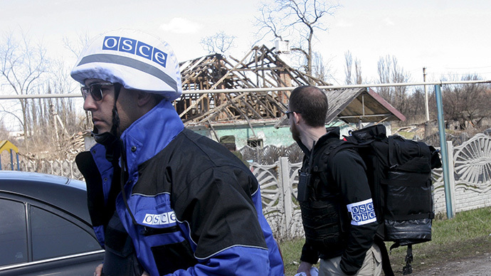 Members of the Special Monitoring Mission of the Organization for Security and Cooperation (OSCE) to Ukraine walk past a house damaged by shelling, in the village of Spartak outside Donetsk April 10, 2015. (Reuters/Igor Tkachenko)