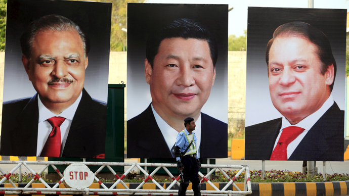 A policeman stands guard next to giant portraits of (L-R) Pakistan's President Mamnoon Hussain, China's President Xi Jinping, and Pakistan's Prime Minister Nawaz Sharif, displayed along a road ahead of Xi's visit to Islamabad April 19, 2015. (Reuters/Faisal Mahmood)