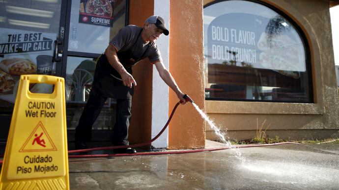 A man waters down the sidewalk outside Taco Bell in Los Angeles, California April 15, 2015. (Reuters/Lucy Nicholson)