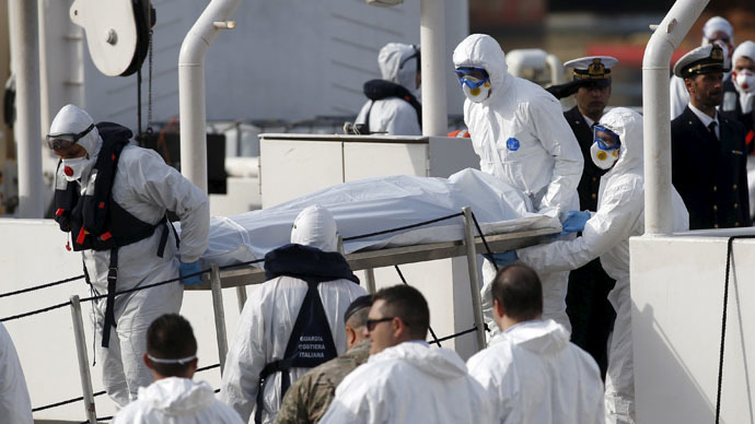 Italian coastguard personnel in protective clothing carry the body of a dead immigrant off their ship Bruno Gregoretti in Senglea, in Valletta's Grand Harbour April 20, 2015. (Reuters/Darrin Zammit Lupi)