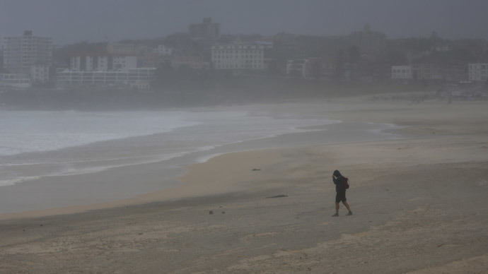 A man walks into a strong wind which stripped Sydney's Bondi Beach of tons of sand as heavy winds blow it inland, April 21, 2015. (Reuters / Jason Reed)