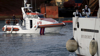 Italian coastguard personnel in protective clothing stand on the deck of their ship 'Bruno Gregoretti', carrying dead immigrants on board, as it arrives in Senglea, in Valletta's Grand, Harbour, April 20, 2015. (Reuters / Darrin Zammit Lupi)