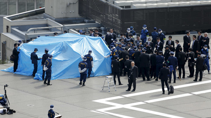Police and security officials stand around a tarpaulin covering a drone on the roof of Prime Minister Shinzo Abe's official residence in Tokyo April 22, 2015. (Reuters / Toru Hanai)