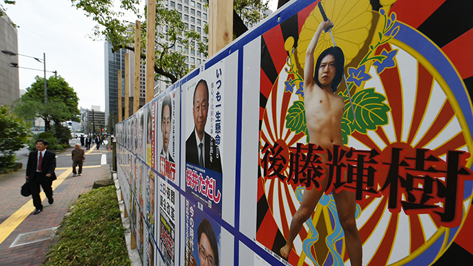Independent candidate for the Chiyoda Ward Assembly Teruki Goto's naked poster is displayed on the campaign board beside the Hibiya park in Tokyo on April 24, 2015 (AFP Photo / Toshifumi Kitamura)
