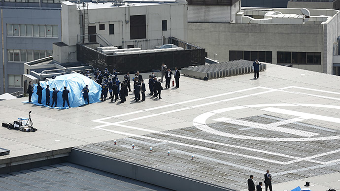 Police and security officials stand around a tarpaulin covering a drone on the roof of Prime Minister Shinzo Abe's official residence  in Tokyo April 22, 2015. (Reuters/Toru Hanai)