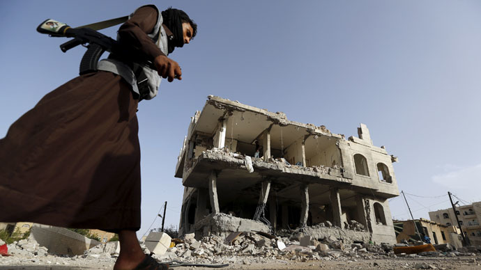A Houthi militant walks past a house destroyed by an air strike in Sanaa April 26, 2015. (Reuters/Khaled Abdullah)