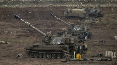 Israeli soldiers stand next to mobile artillery units near the border with Syria in the Golan Heights (Reuters/Baz Ratner)