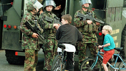 Young boys with their bikes chat to armed British soldiers on the Peace Line in West Belfast August 10, 1997 (Reuters)