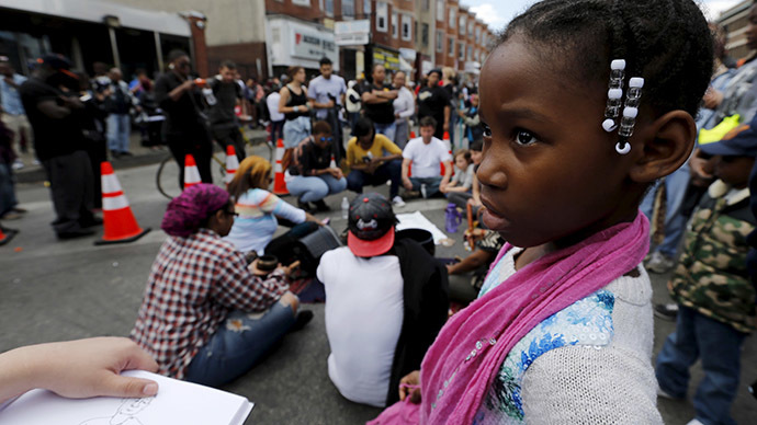 A young girl stands with a group of peaceful demonstrators outside a recently looted and burned CVS store in Baltimore, Maryland, United States April 28, 2015. (Reuters/Jim Bourg)