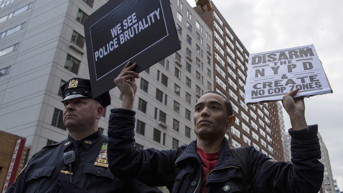 A protester holds signs during a demonstration calling for social, economic and racial justice in New York May 1, 2015. (Reuters/Brendan McDermid)