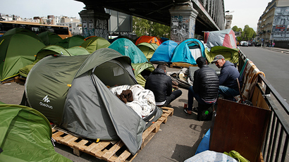 Migrants gather near tents as they live in a make-shift camp under a metro bridge in Paris, France (Reuters / Benoit Tessier)