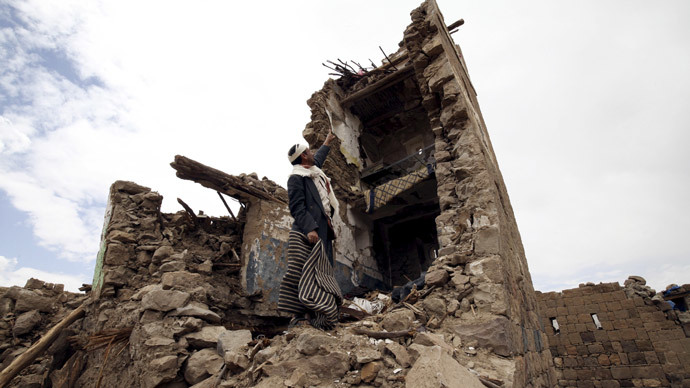 A man points up at a house that was damaged during an airstrike carried out by the Saudi-led coalition in Faj Attan village, Sanaa, Yemen May 7, 2015. (Reuters / Mohamed al-Sayaghi)
