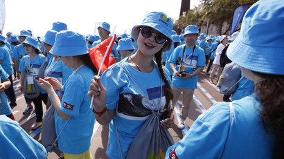 "Employees of Chinese company ""Tiens"" attend a parade on May 8, 2015 in Nice organized by ""Tiens"" CEO Li Jinyuan as part of the two-days celebration weekend for the 20th anniversary of his company in which he invited 6,400 of his employees. (AFP Photo / Valery Hache)"