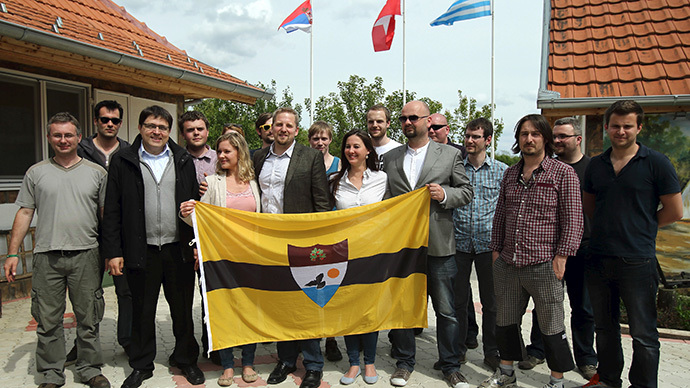 "Self-proclaimed president of the ""Free Republic of Liberland"" Vit Jedlicka (C)  poses with the Liberland flag and future citizenships in the village of Backi Monostor, Serbia May 1, 2015. (Reuters/Antonio Bronic)"