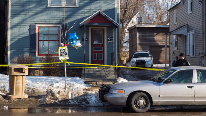 A makeshift memorial pays tribute to a 19-year-old black man killed by police, as an officer guards the 1100 block of Williamson Street in Madison, Wisconsin March 7, 2015 (Reuters / Tom Lynn)