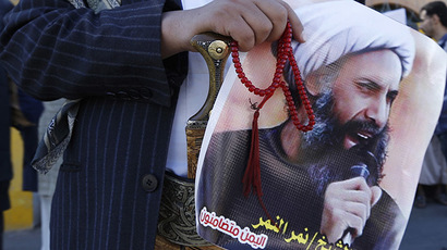 A Shi'ite protester carries a poster of Sheikh Nimr al-Nimr. (Reuters/Khaled Abdullah)