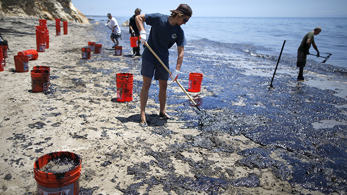 William McConnaughey, 56, (R) who drove from San Diego to volunteer, carries buckets of oil from an oil slick in bare feet along the coast of Refugio State Beach in Goleta, California, United States, May 20, 2015 (Reuters / Lucy Nicholson)
