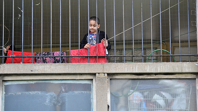 A child plays behind railings on the Robin Hood Gardens estate in Poplar, in East London (Reuters / Jas Lehal)