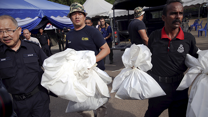 Forensic policemen carry body bags with human remains found at the site of human trafficking camps in the jungle close the Thailand border after they brought them to a police camp near Wang Kelian in northern Malaysia May 25, 2015 (Reuters / Damir Sagolj)