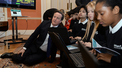 Britain's Prime Minister David Cameron sits on the floor as he joins students for