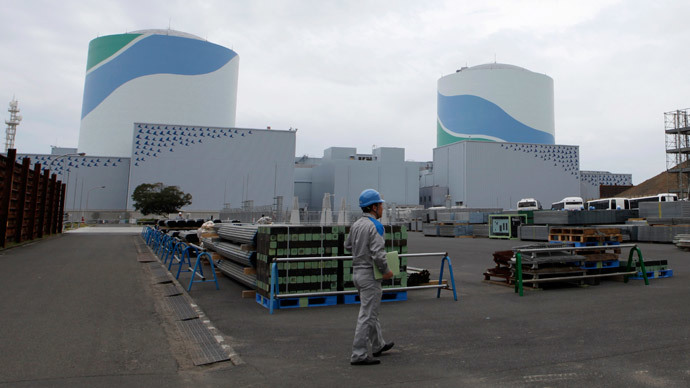An employee of Kyushu Electric Power Co walks in front of reactor buildings at the company's Sendai nuclear power plant in Satsumasendai.(Reuters / Mari Saito )