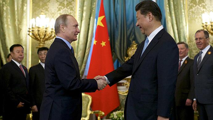 Russia's President Vladimir Putin (L) shakes hands with China's President Xi Jinping. (Reuters/Alexander Zemlianichenko)
