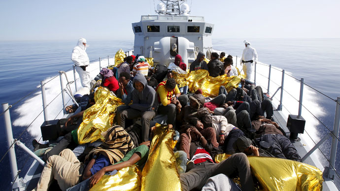 A group of 300 sub-Saharan Africans, sit aboard the Italian Finance Police vessel Di Bartolo during a rescue operation off the coast of Sicily, May 14, 2015. (Reuters/Alessandro Bianchi)